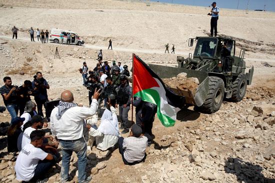 الفلسطينيون يرفعون علم بلادهم أمام جرافات الاحتلال الإسرائيلى