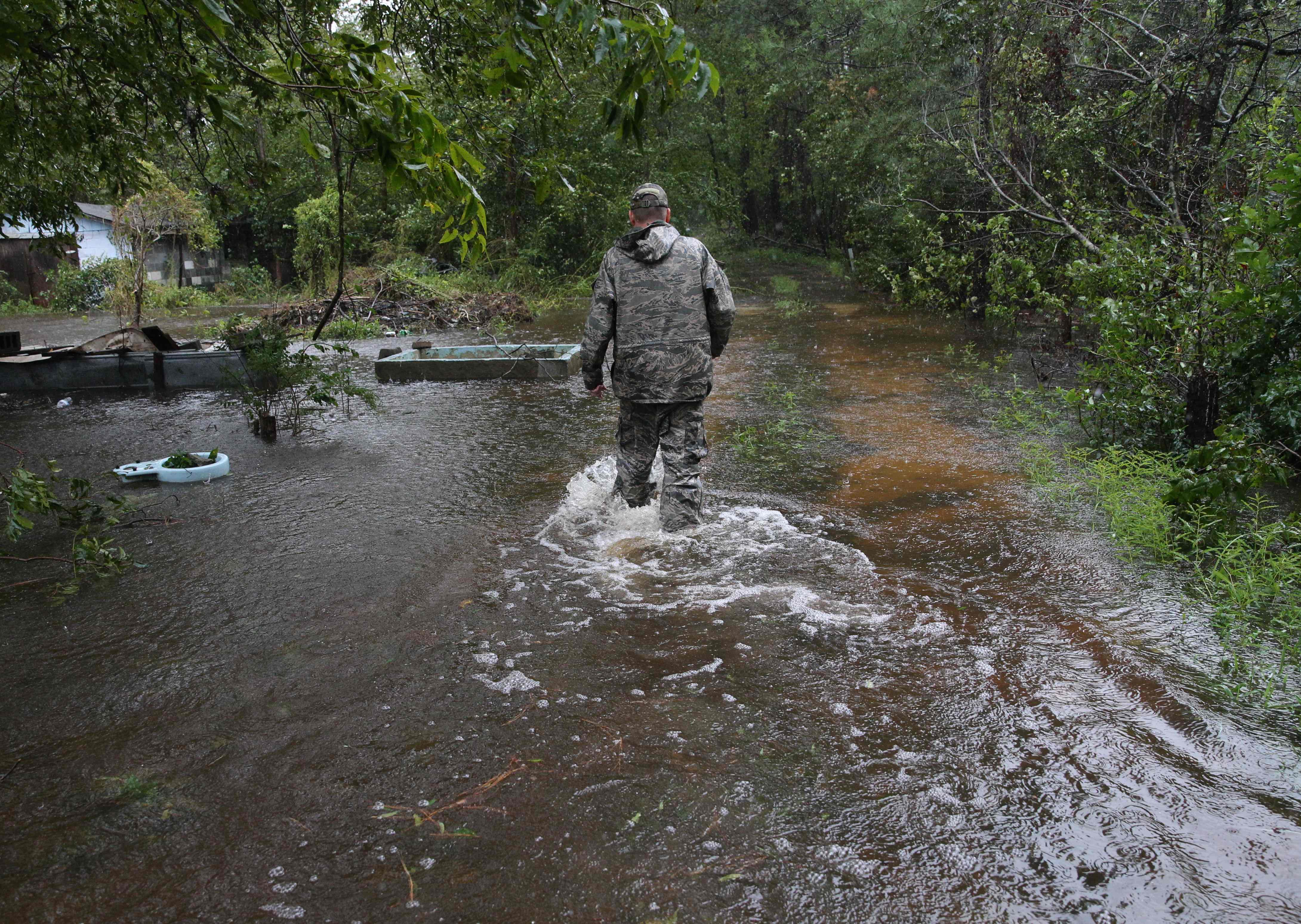أحد رجال الإنقاذ يسير وسط الأمطار