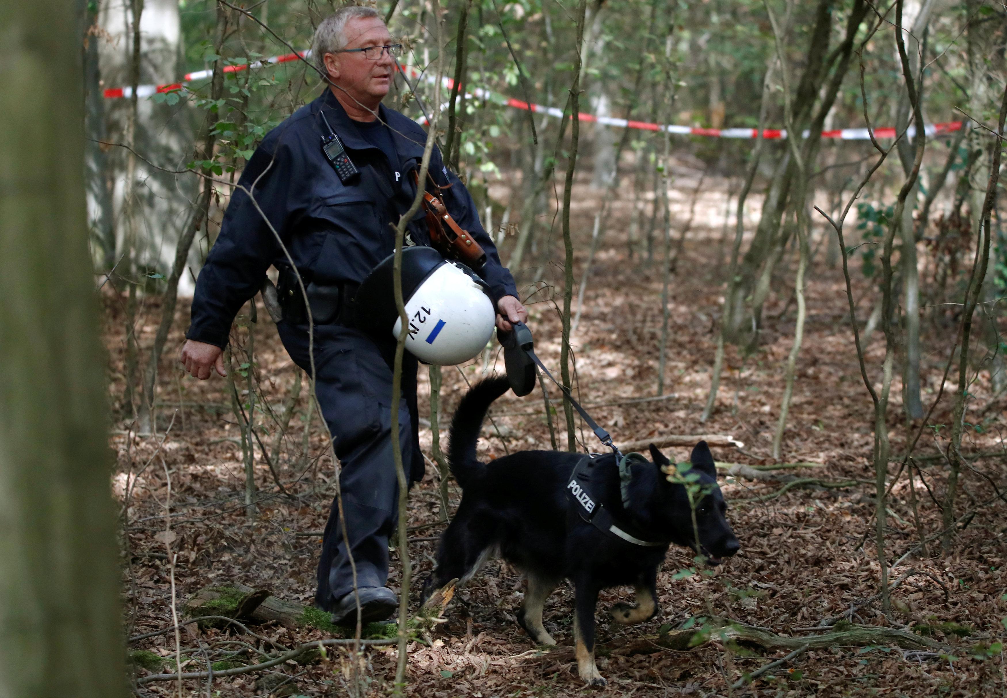 أحد أفراد الشرطة الألمانية يتجول بصحبة كلب بوليسى لتمشيط الغابة