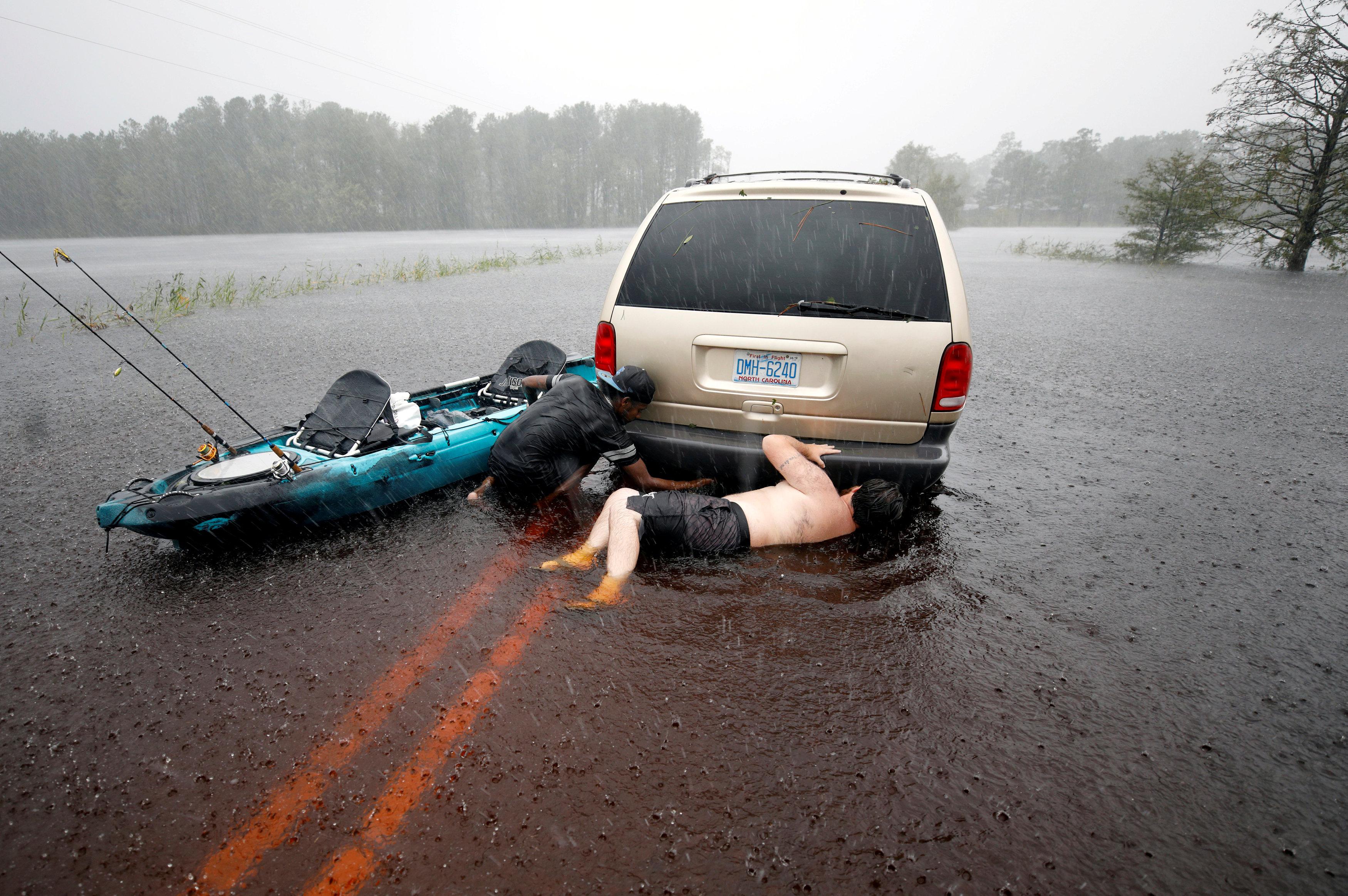 محاولات لإصلاح سيارة تعطلت بسبب المياه