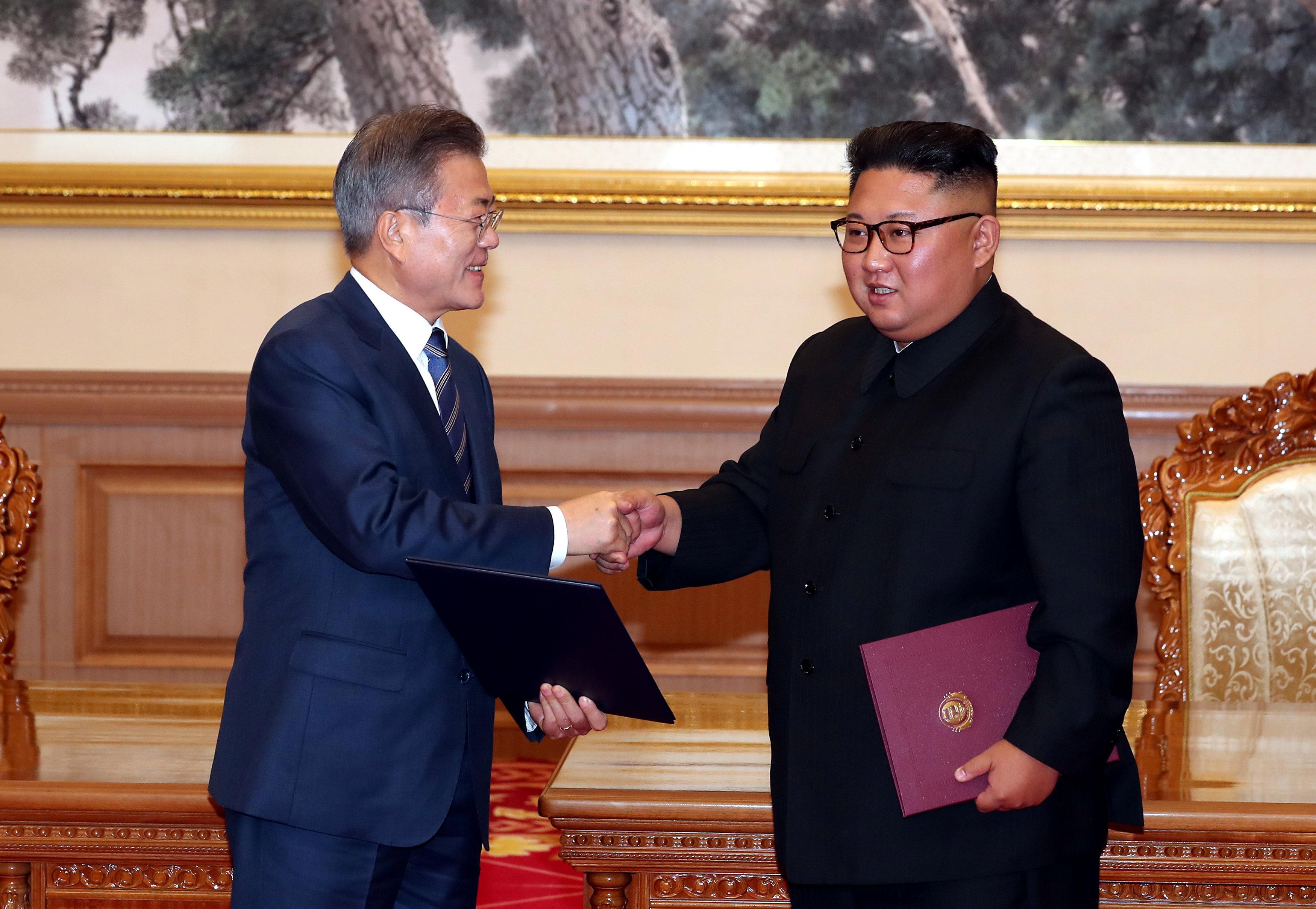 كيم يصافح مون بعد التوقيع على عدد من الاتفاقات