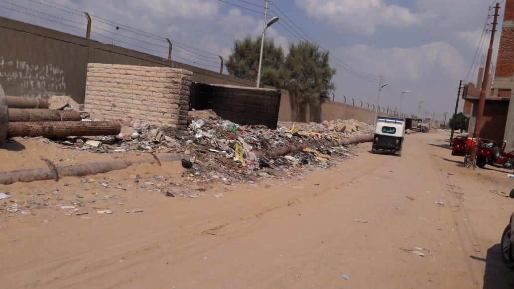 2- تراكم القمامة بالطريق الرئيسى بالقرية
