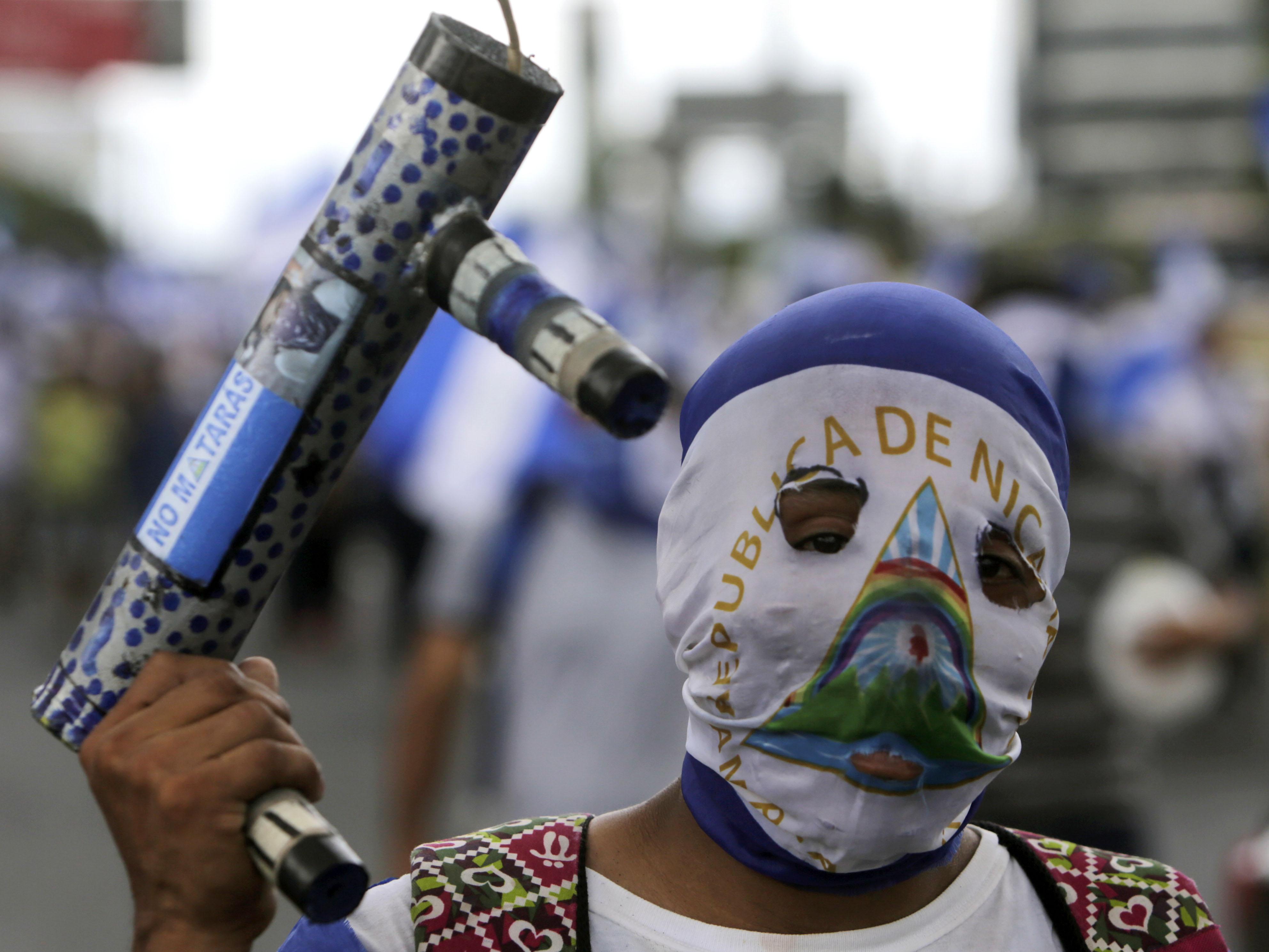 متظاهر يحمل سلاح هاون فى الاحتجاجات
