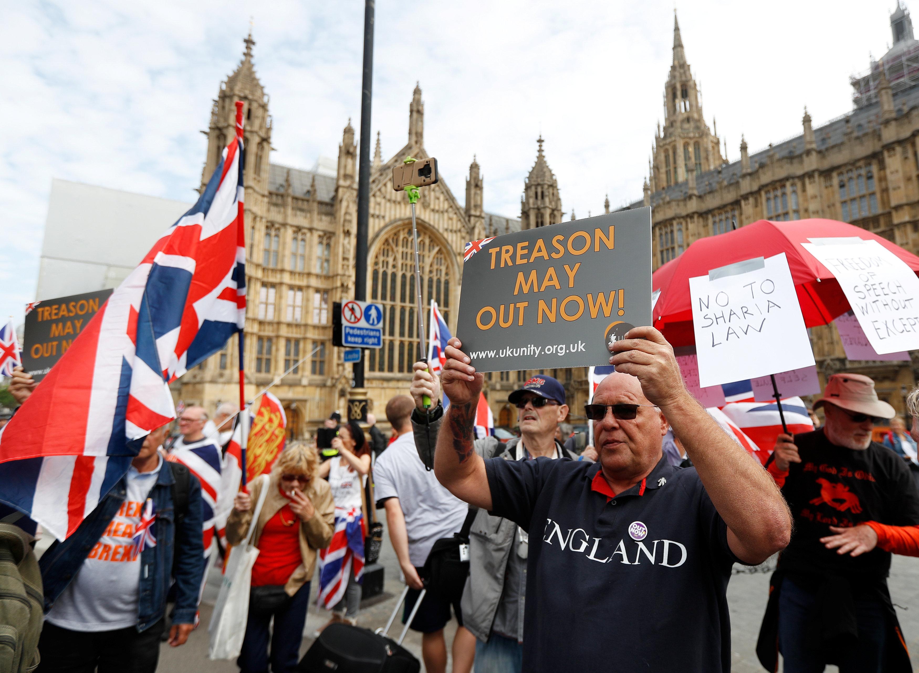 مجموعة من المتظاهرين يرفعون لافتات مناهضة لسياسات الحكومة البريطانية