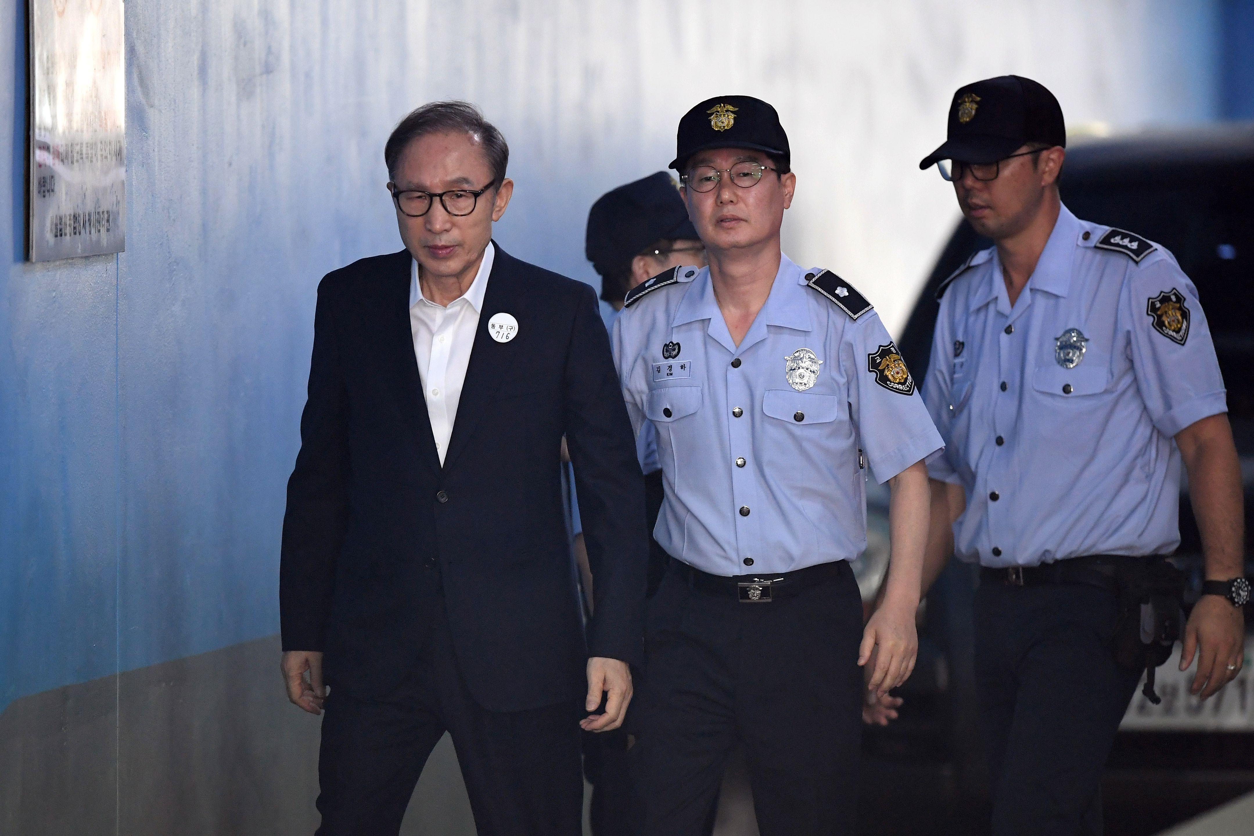 عناصر الشرطة ترافق لي ميونج باك للمحكمة