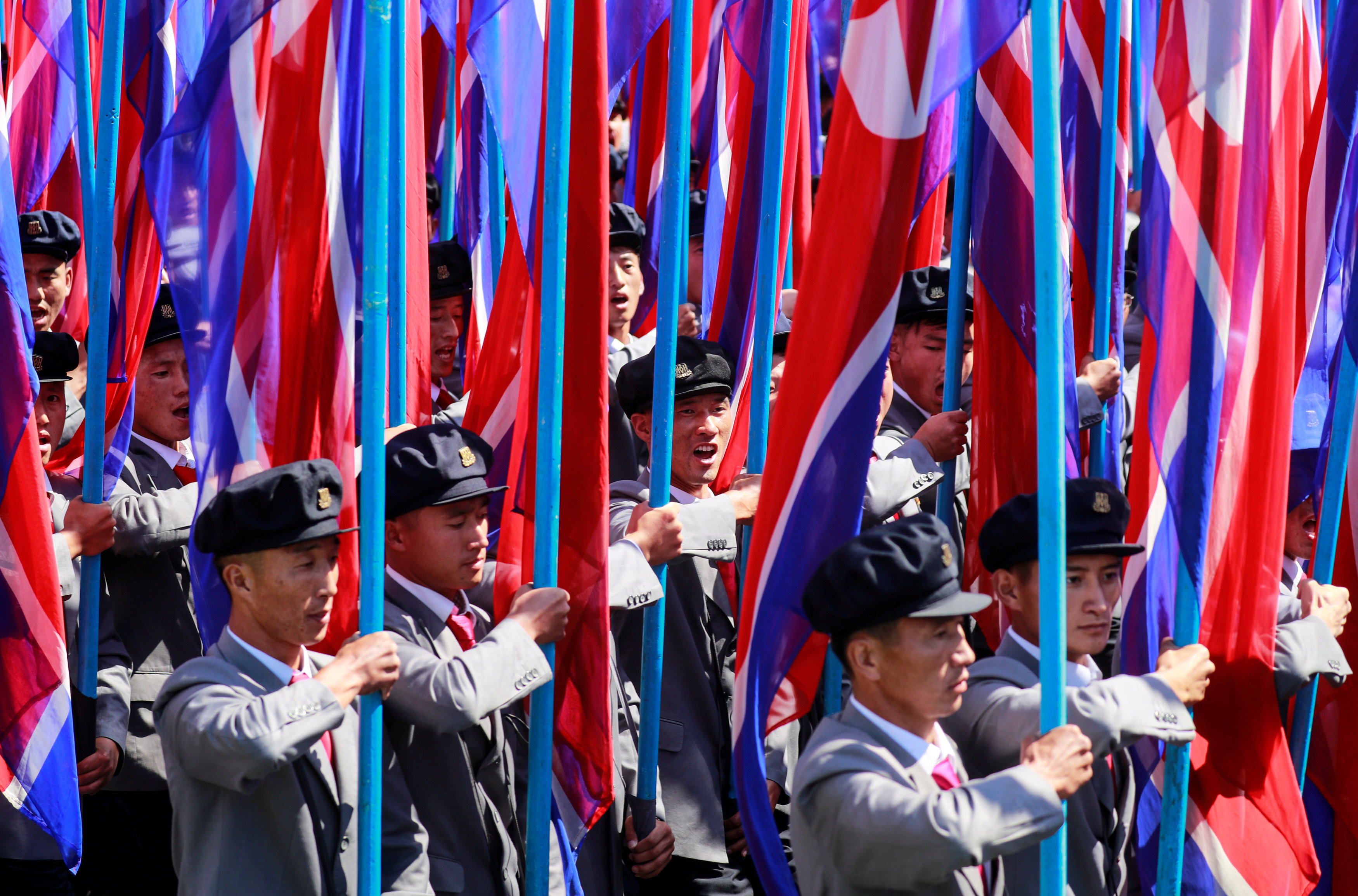 حمل أعلام كوريا الشمالية خلال العرض العسكرى