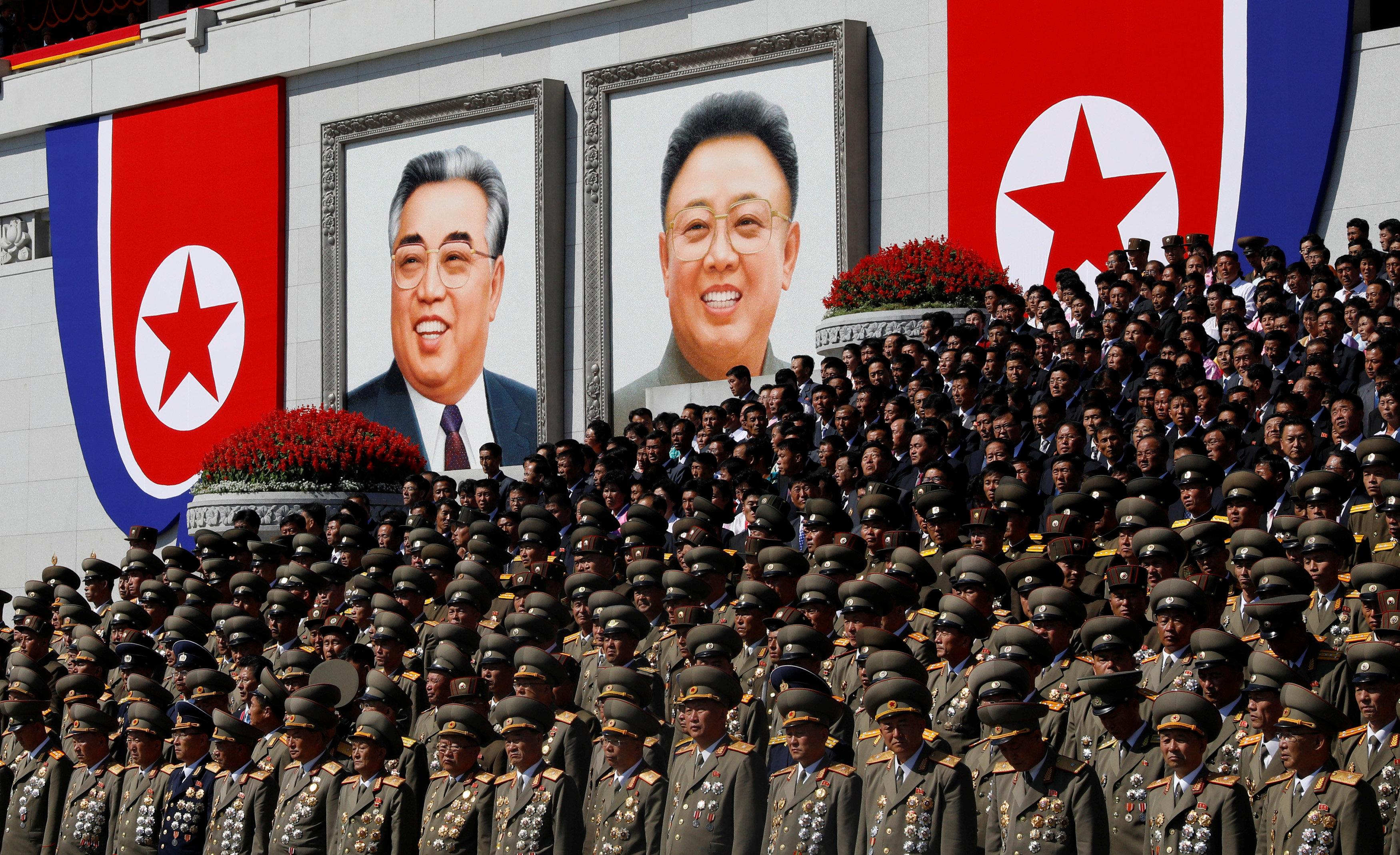 الضباط العسكريون يقفون بالقرب من صور مؤسس كوريا الشمالية