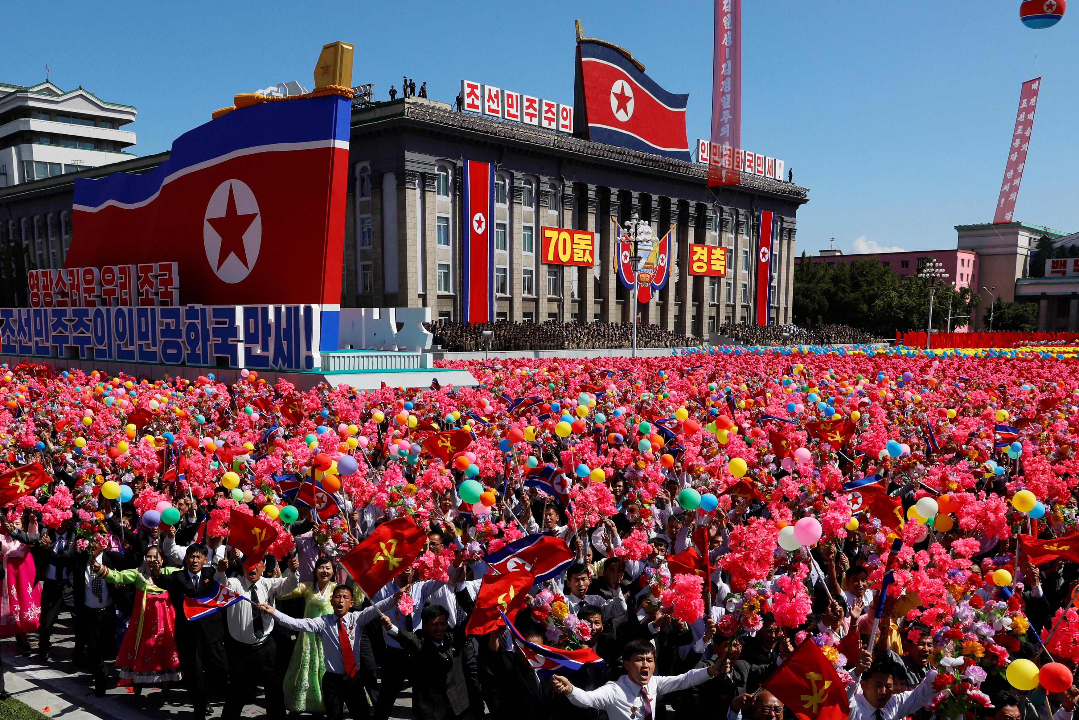 الناس يرفعون الزهور البلاستيكية والبالونات خلال العرض العسكرى