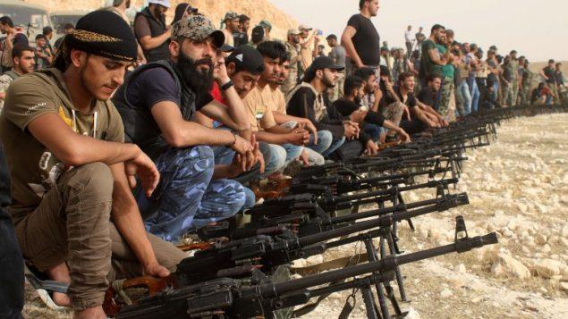 مقاتلو معارضة سوريون يجلسون خلف رشاشات اسرائيلية بدرعا،