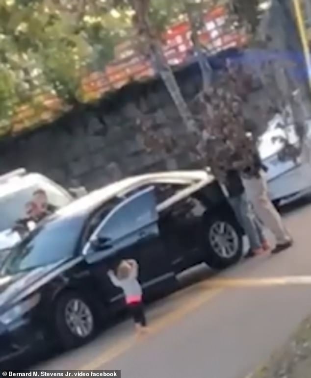 Shocking-moment-barefoot-toddler-walks-with-her-hands-in-the-air-towards-armed-police