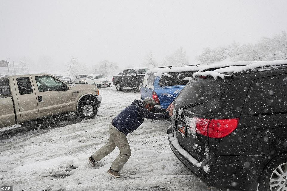 رجل يحاول أن يخرج سيارته من وسط الثلوج فى ولاية يوتا