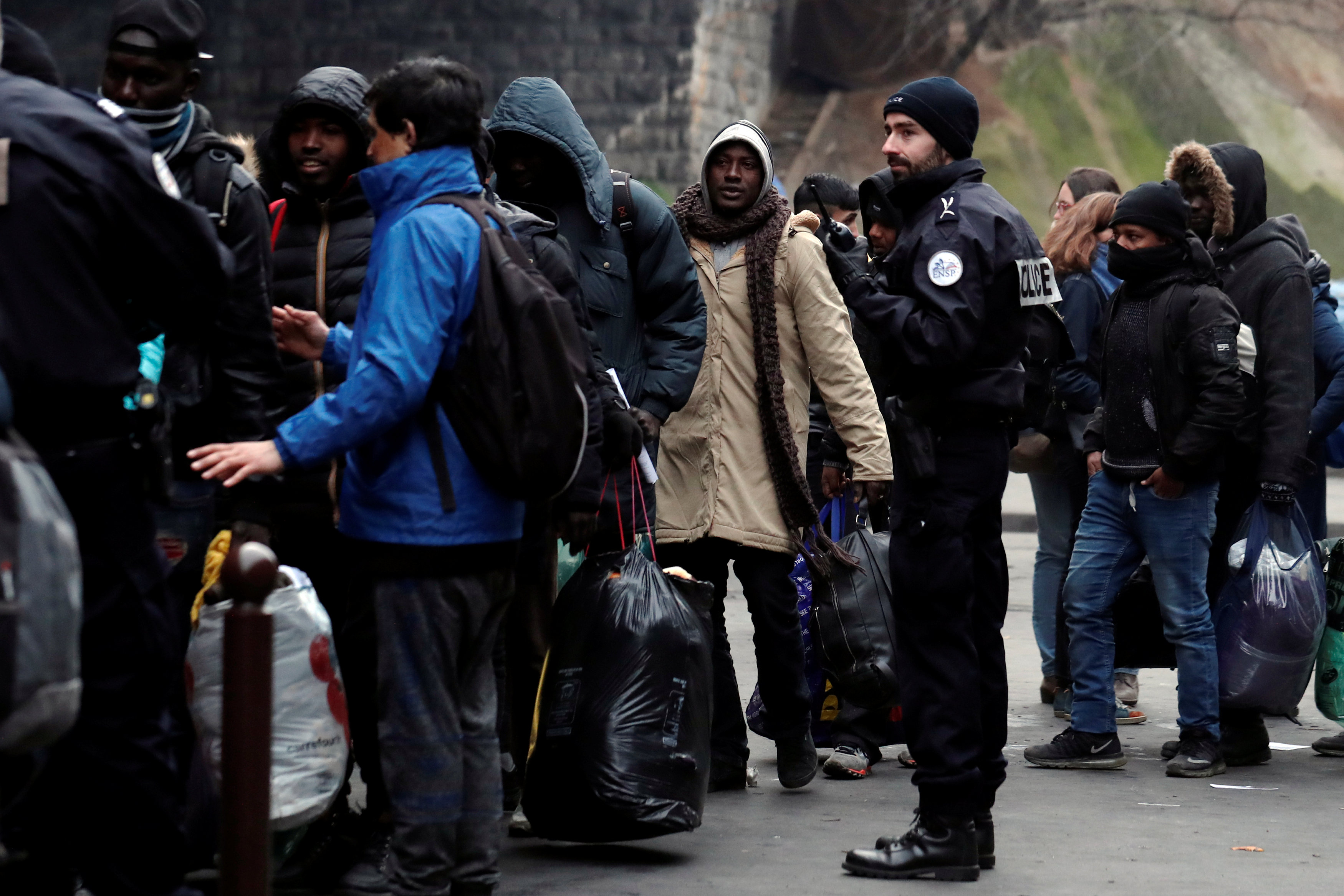 أحد أفراد الشرطة الفرنسية يتابع اللاجئين