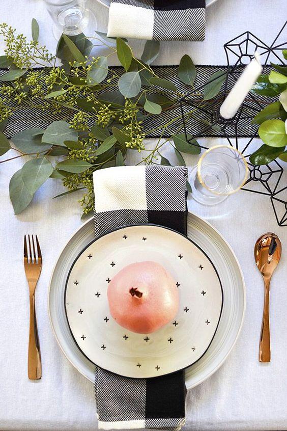 طاولة أنيقة أحادية اللون ومساحات خضراء وشموع بيضاء ومناديل مطبوعة وألواح ذهبية
