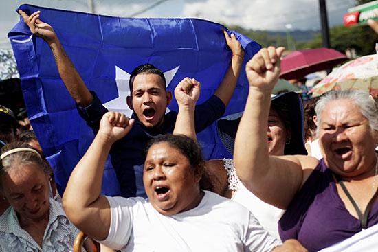 مؤيدو رئيس هندوراس خوان أورلاندو هرنانديز يلمحون خلال مسيرة لدعمه