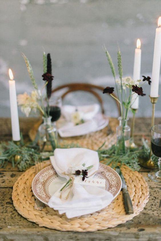 طاولة بسيطة مع المفارش المنسوجة ، والشموع  الطويلة ، ومساحات خضراء