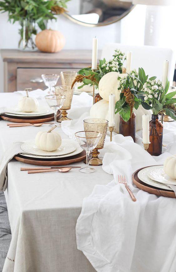 طاولة طعام أنيقة مع شواحن خشبية ، والشموع ، وزجاجات الصيدلي بالإضافة إلى القرع الأبيض
