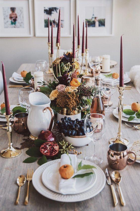 طاولة طعام عليها شموع طويل ، ولمسات من النحاس والذهب والخزف الأبيض بالإضافة إلى الإزهار