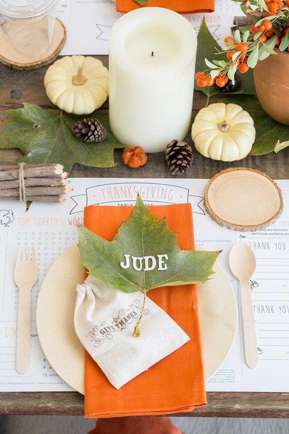 طاولة بسيطة مع أوراق الخريف والتوت والقرع والشموع عمود ولمسات من اللون البرتقالي