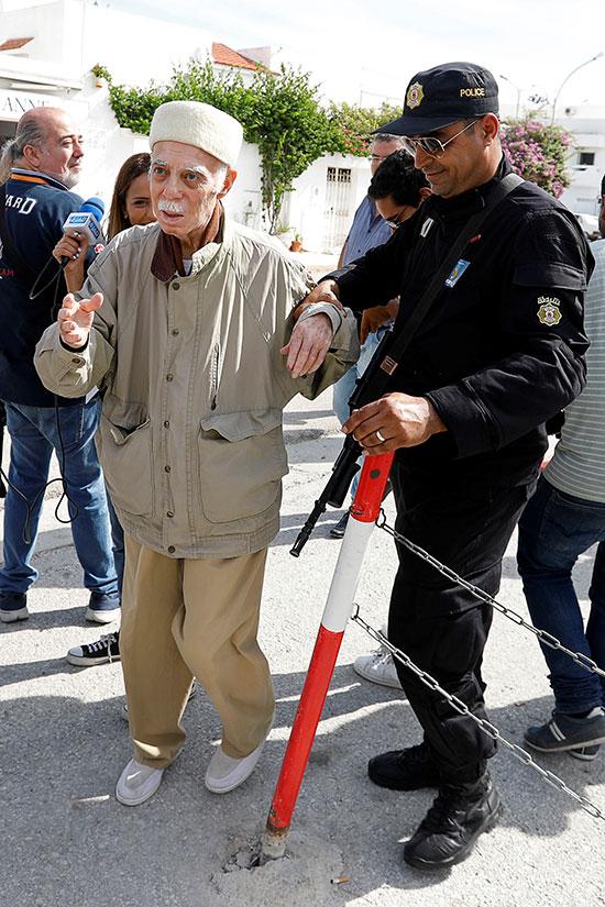رجل يساعده أحد أفراد الشرطة أثناء وصوله للإدلاء بصوته