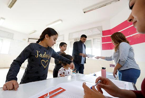 فتاة تلطخ بإصبعها بالحبر أثناء حضور والدها للتصويت في مركز اقتراع