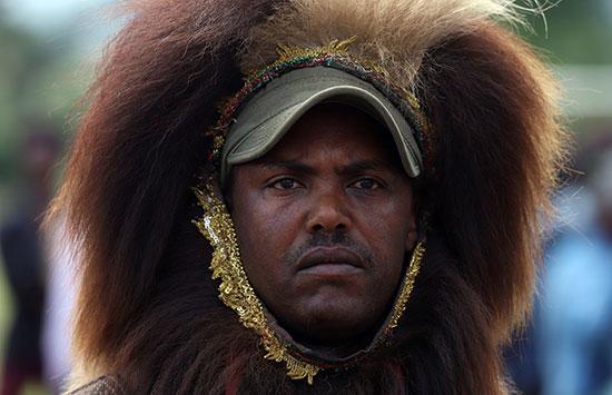 رجل يرتدي شعارات من السكان الأصليين يحتفل برئيس الوزراء الإثيوبي