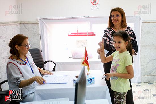 مواطنة تصطحب ابنتها أثناء الإدلاء بصوتها