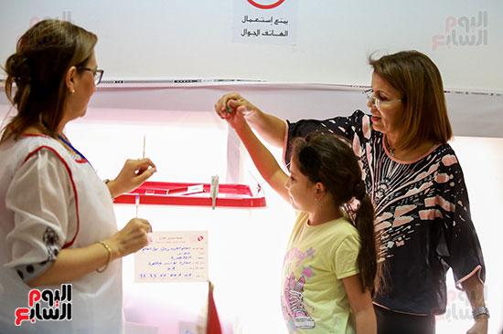 طفلة تونسية تشارك والدتها أثناء الإدلاء بصوتها