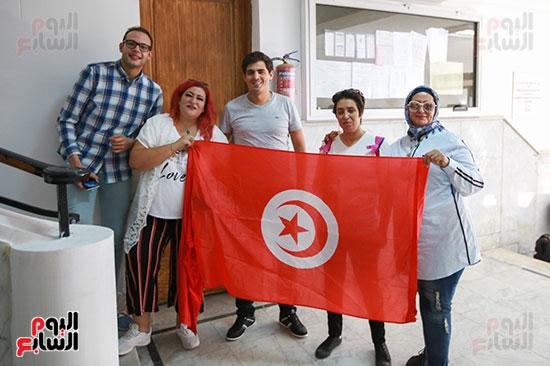 التونسيون يرفعون علم تونس بالسفارة عقب الإدلاء بأصواتهم