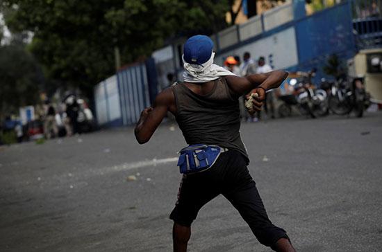 متظاهر يلقى بالحجارة