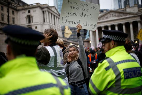 ناشطة-ترفع-لافتة-للمطالبة-بإجراءات-للقضاء-على-التغيرات-المناخية
