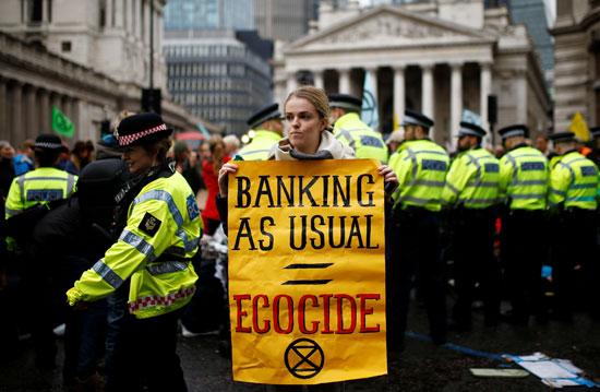 ناشطة-تحمل-لافتة-مناهضة-لتقاعس-الحكومة-البريطانية-فى-التعامل-مع-تغيرات-المناه