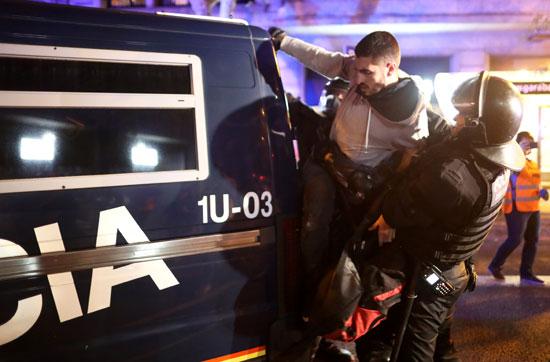 شرطى يلاحق أحد المتظاهرين