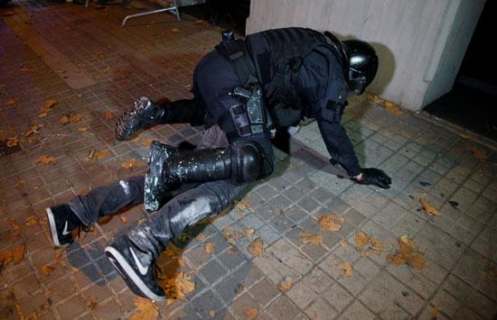 شرطى يعتقل أحد المتظاهرين