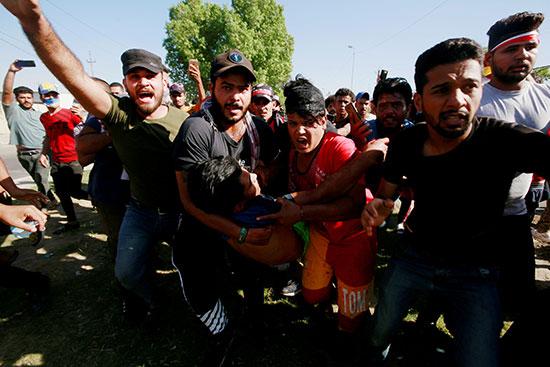 رجال يحملون متظاهرًا مصابًا في احتجاج أثناء حظر التجول