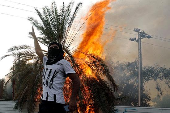 محتج يقف بجوار شجره محترقة