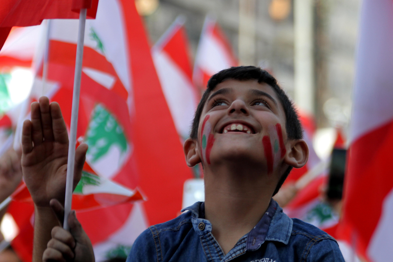 طفل يرسم العلم اللبنانى على وجهه فى مظاهرة بطرابلس