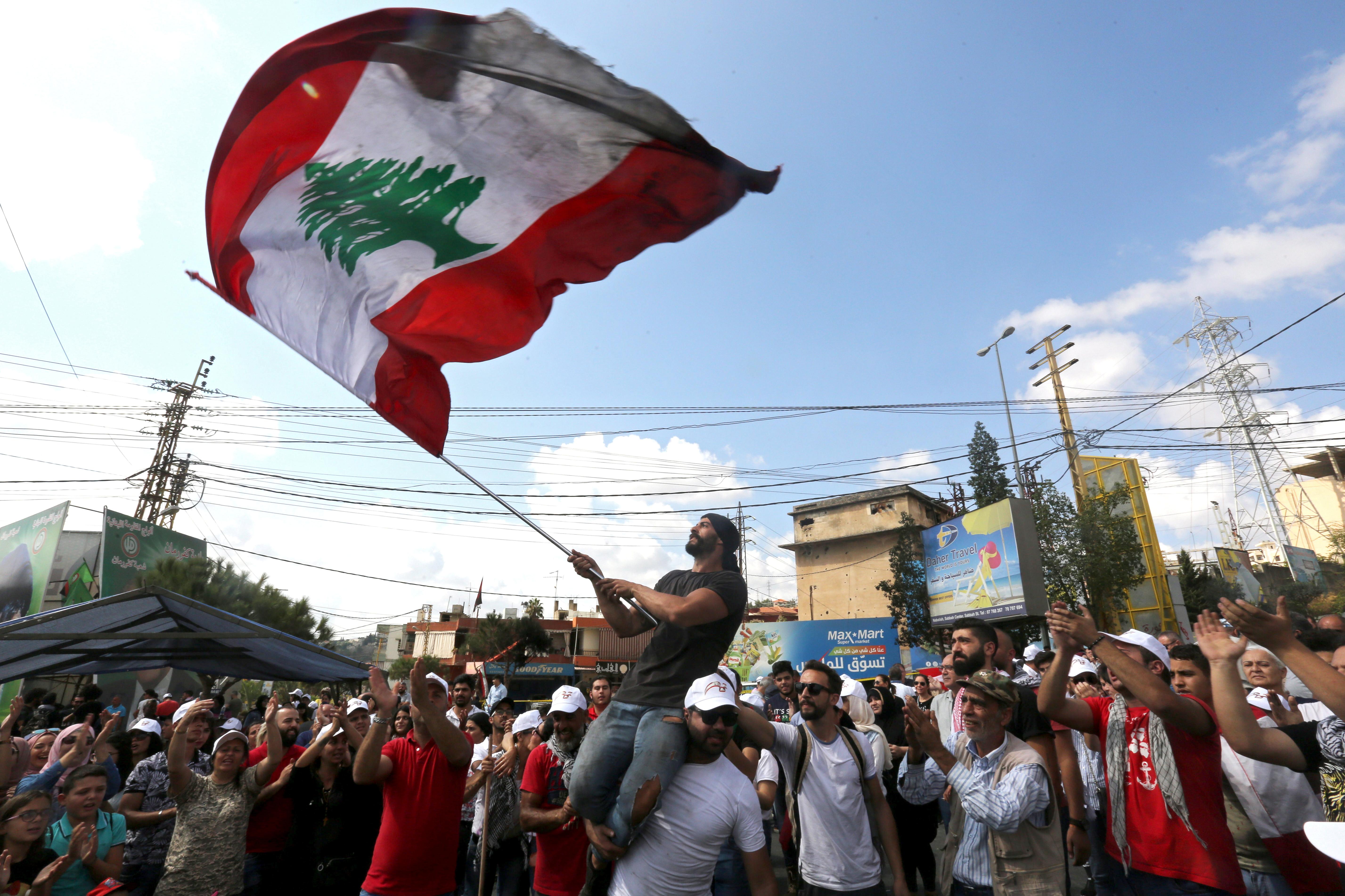 متظاهر يلوح بعلم وطني خلال مظاهرة  في مدينة النبطية الجنوبية
