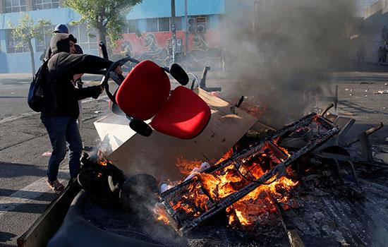 متظاهر يحرق كرسى فى تشيلى