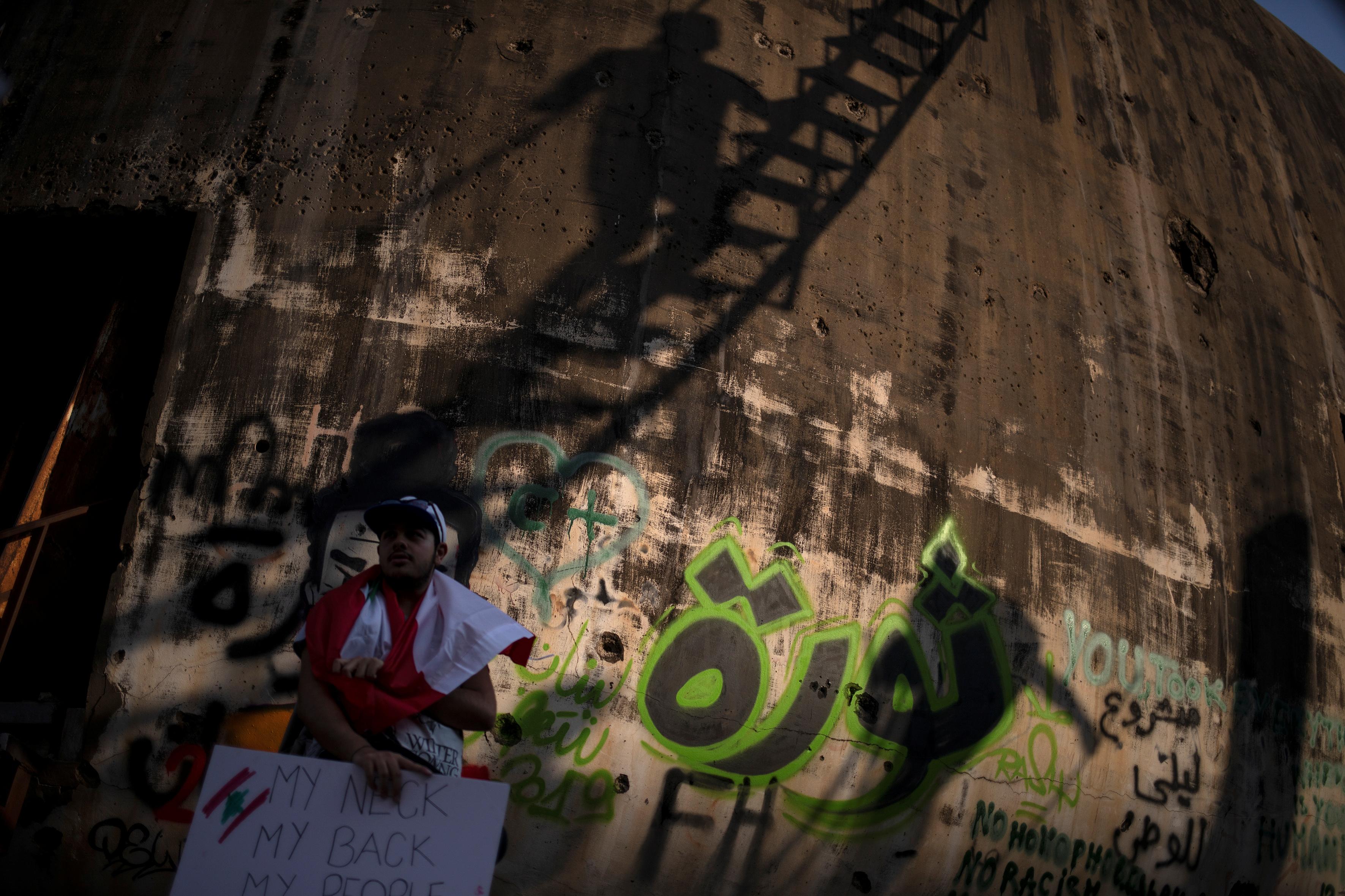 مواطن لبنانى يقف امام حائط مكتوب علية كلمة ثورة