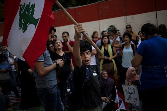 طفل مشارك فى المظاهرات يلوح بالعلم اللبنانى