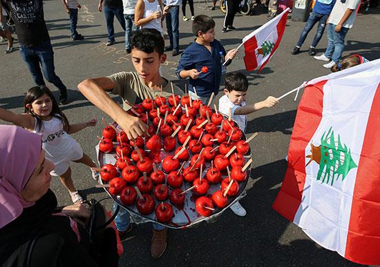 أطفال يحملون العلم الوطنى اللبنانى أثناء قيام صبي ببيع تفاح الكراميل