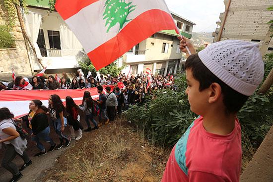طفل-يرفع-العلم-اللبنانى-خلال-مسيرة-احتجاجية