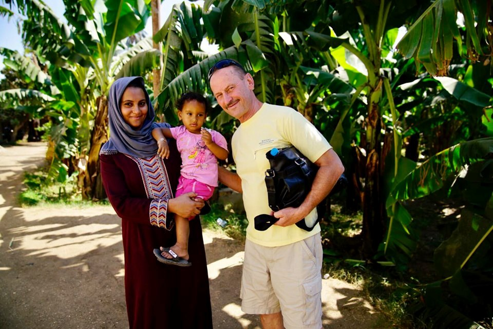 عضو فى الأوركسترا الأوكرانية يلتقط صورة مع سيدة وطفلها غربى الأقصر