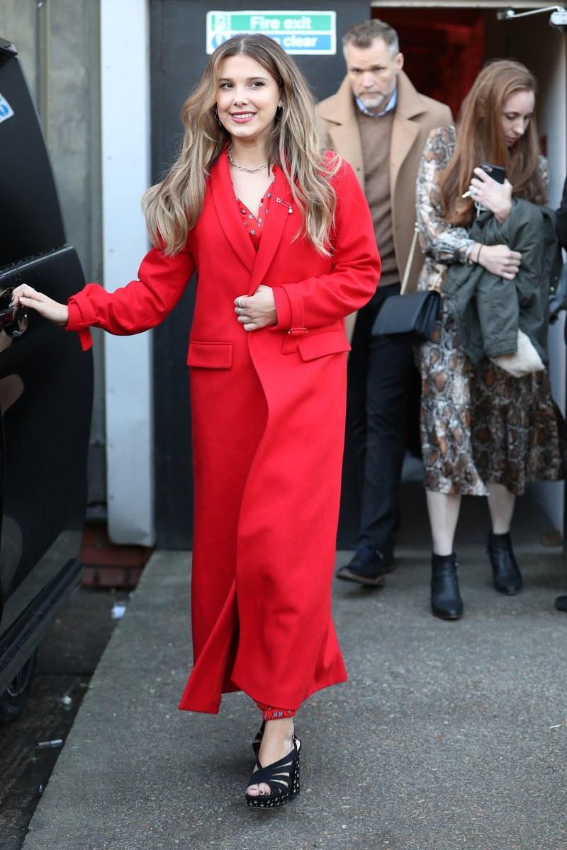 ميلي بوبي براونترتدى بالطو أحمر  من الصوف