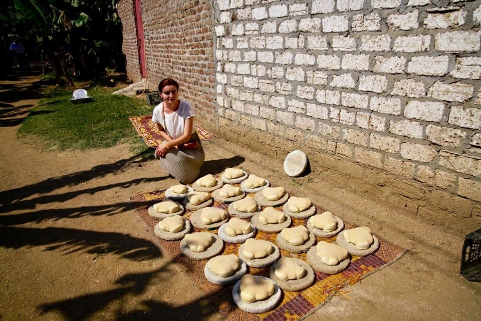 عضو فى الأوركسترا الأوكرانية تلتقط صورة تذكارية مع الخبز البلدى قبل إنهاؤه بالأقصر