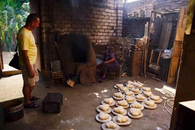 عضو بفريق الأوركسترا الأوكرانية يشهد طهى الخبز البلدى فى الفرن بالاقصر