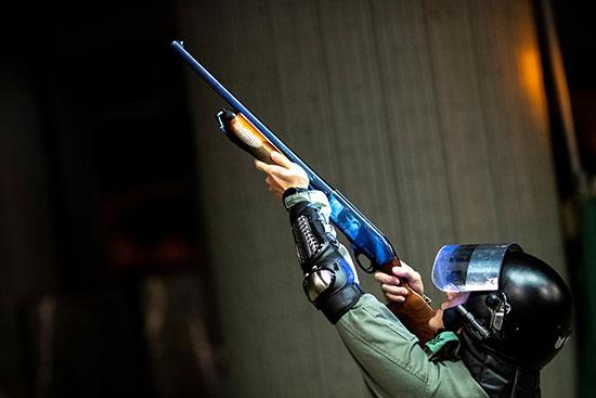 ضابط شرطة مكافحة الشغب يصوب بندقية باتجاه المتظاهرين المناهضين للحكومة