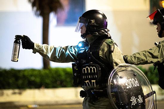 ضابط شرطة مكافحة الشغب يشير إلى رش الفلفل