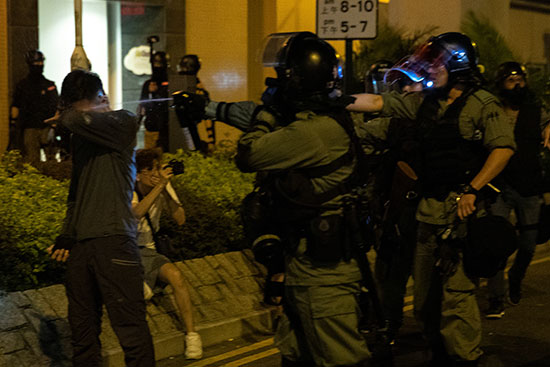 ضابط شرطة مكافحة الشغب يستخدم رذاذ الفلفل تجاه متظاهر مناهض للحكومة