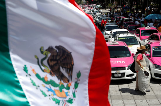 العلم المكسيكي يرفرف بينما ينظم سائقي سيارات الأجرة احتجاجًا على تطبيقات التاكسي الذكية